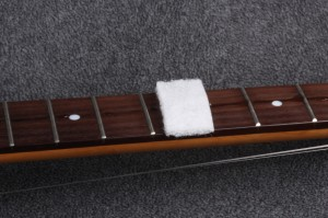 Using the pad, gently clean at a 90 degree to the fingerboard (same direction as frets)